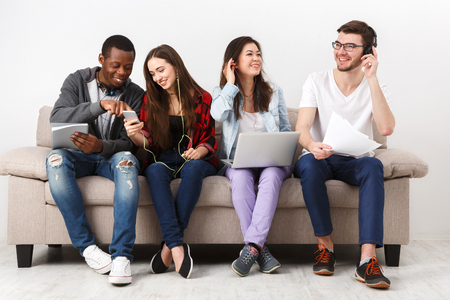 Multiethnic international students listen to music with gadgets, sitting together on couch indoors. Modern education.