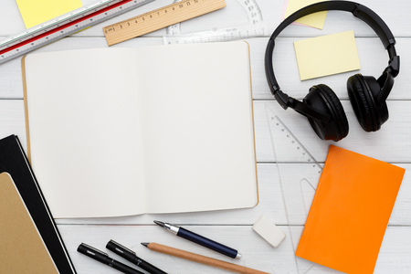 home office interior: Stationery supplies in modern office workspace. Top view on open blank notebook, pen, pencil, rulers, small notepads and memo pads, headphones on white wooden desktop, flat lay, copy space, mockup