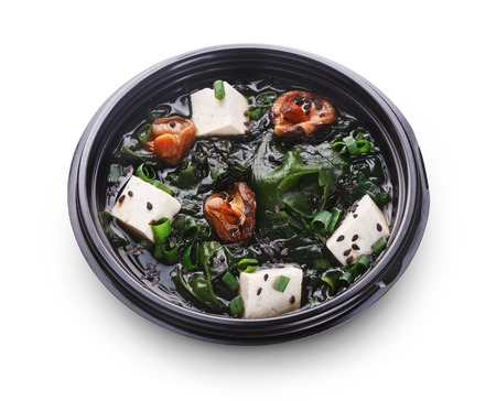 Japanese food delivery. Miso soup with tofu cheese, mushrooms and seaweed in black take away plate isolated at white background