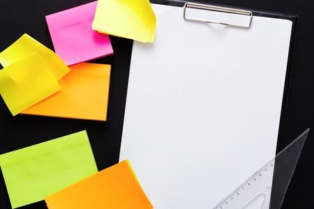 학교 편지지입니다. 다채로운 스티커 메모, 눈금자 및 검은 색 바탕에 빈 메모 용지에 상위 뷰. 복사 공간이있는 체크리스트를위한 모형
