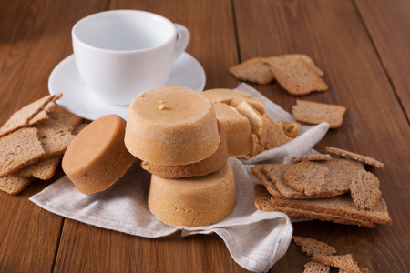 Norwegian homemade brown cheese brunost with crackers and empty cup on wooden desk, close-up, selective focus