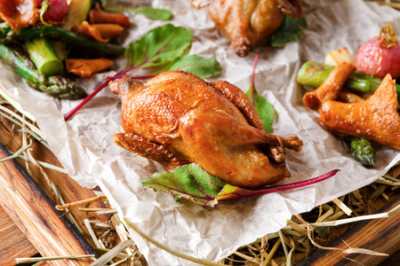 Excuisite restaurant food. Quails baked to golden crust with asparagus and chanterelles on grungy wooden platter on craft paper. Freshly cooked meals on rustic background with copy space, closeup