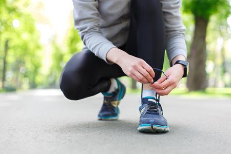 Bindende de schoenenkant van de vrouw alvorens te lopen, die klaar voor het aanstoten in park, close-up worden
