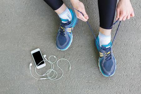 Bindende de schoenenkant van de vrouw alvorens te lopen, die klaar voor het aanstoten in park, hoogste mening worden