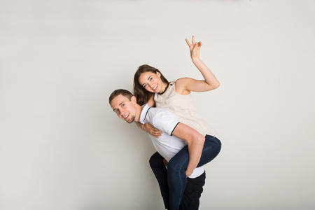 Loving couple piggybacking. Happy young man with his girlfriend posing for camera, having fun together Stock Photo