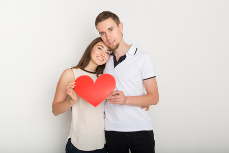 Young happy couple in love holding red paper heart, smiling at camera, copy space Stock Photo