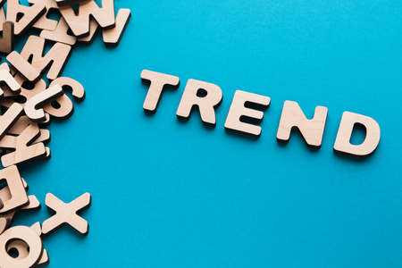 Word Trend on blue background, with pile of wooden english letters. Popular things concept Stock Photo