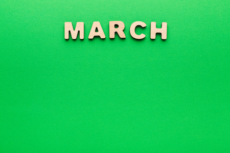 Word March made of wooden letters on green background. Month planning, timetable concept
