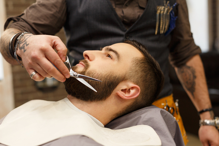 hairdresser: Barber make beard haircut with scissors in barbershop, closeup of clients head. Hairstyle in barbershop. Stock Photo