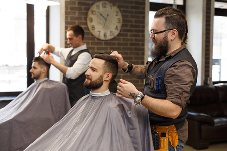 mirror: Barber make haircut with scissors at barbershop. Stylish hairdresser in male hair salon Stock Photo