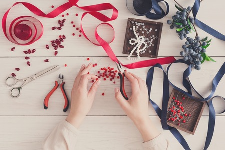 scrunchie: Woman making jewelry, home workshop. Artisan pov, female hands creating accessory with beads and ribbons, top view. Beauty, creativity, handicraft concept Stock Photo
