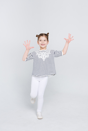 Emotional full length portrait of cunningly smiling girl showing her palms at studio on white background. Funny sly child displaying empty hands, posing on camera, copy space Stock Photo