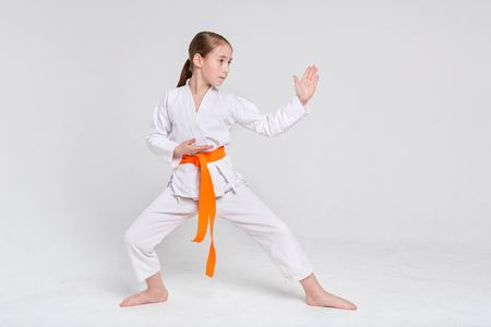 Karate girl in stand at white studio background. Sporty teenager in kimono practicing martial arts. Healthy lifestyle, active childhood and self defense concept, copy space