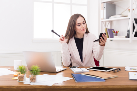 Young business woman refreshing her makeup looking at compact mirror sitting at her workplace in office