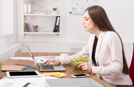 Business woman working on laptop at office. Businesswoman typing something on computer while sitting at her working place, copy space Stock Photo