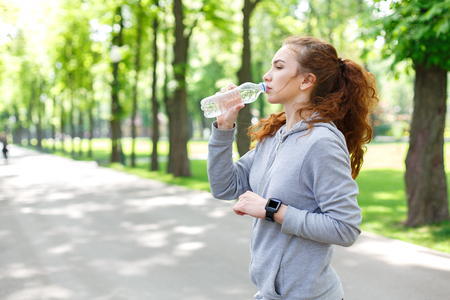 Young woman runner is having break, drinking water while jogging in park