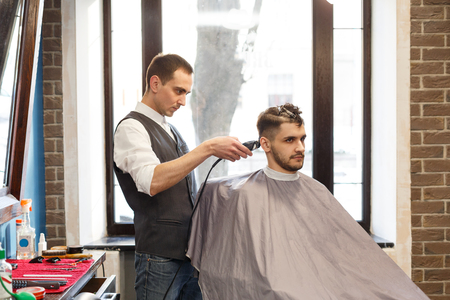 hairdresser: Barber make beard haircut with trimmer hair clipper in barbershop. Hairstyle in barbershop. Stock Photo
