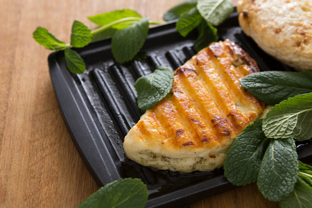 Halloumi roasted on grill cypriot cheese served with mint on wooden desk, close-up, selective focus Stock Photo