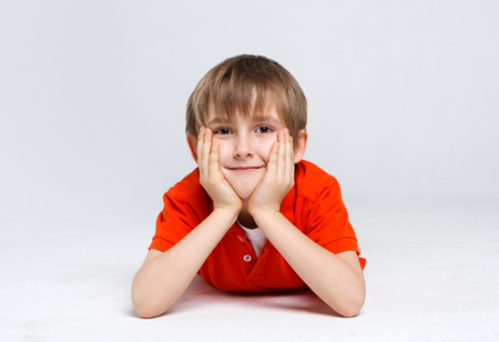 Portrait of a dreamy boy lying on the floor at white studio background. Kid in casual bright clothes posing on camera, copy space Stock Photo