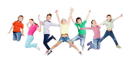 Grupo de niños alegres, alegres que saltan en el fondo blanco aislado del estudio. Niñez y libertad, concepto de estilo de vida activo, espacio de la copia