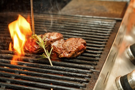 Meat steaks bbq with rosemary on open fire. Fresh restaurant food cooked on professional grill outdoors. Reklamní fotografie