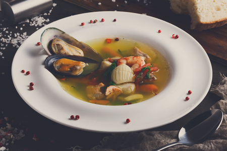 French cuisine restaurant. Seafood soup with white fish, shrimps and mussels in plate sprinkled with spices. Freshly cooked exclusive meals on wooden table