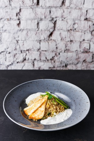 Healthy gourmet restaurant lunch. Quinoa salad with avocado, cucumber, halloumi cheese and tsadziki sauce in gray plate on black background. Traditional greek cuisine. Copy space