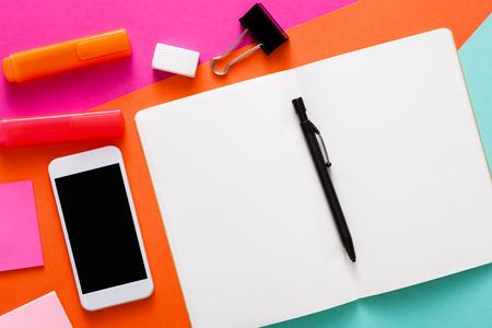 Creatief minimaal ontwerp, platte lay-out van de werkruimte met briefpapier, smartphone, open lege Kladblok. Abstracte kleurrijke achtergrond met kopie ruimte op schetsboek, bovenaanzicht, mockup Stockfoto - 84043985