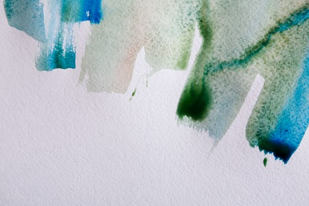 ink stain: Watercolor paint brush strokes background. Abstract color spots on white paper texture, top view, copy space