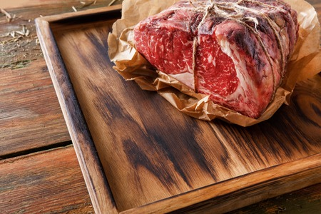 Raw black angus beef bound with rope in craft paper on cutting board. Aged prime marble meat at rustic wood background, closeup, copy space