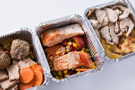 Healthy food delivery. Take away of natural fitness dishes for diet. Daily meals in foil boxes on white background, closeup Stock Photo