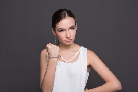 Young attractive woman showing punch gesture. Girl with fist, posing and looking at camera. Stock Photo