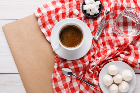 servilleta de papel: Morning coffee at restaurant. White porcelain cup of black bitter coffee with treats on stylish checkered tablecloth and craft paper on wooden background, top view, copy space