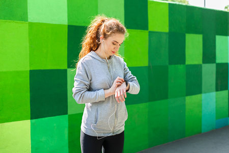 Young woman using smart watch standing at bright colorful graffiti wall background Stock Photo