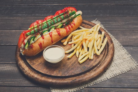 Hot dog and french fries. American fast food restaurant cuisine on wooden platter on table. Stock Photo