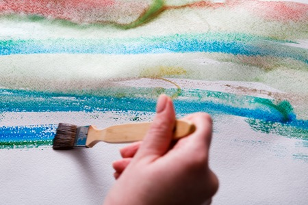 Artist creating watercolor painting. Expressive brush strokes of blue aquarelle on paper texture. Modern art backgroung with copy space Stock Photo