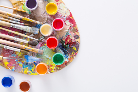 Artists palette with colorful paint strokes, gouache jars and paintbrushes on white isolated background, top view, flat lay, object Stock Photo