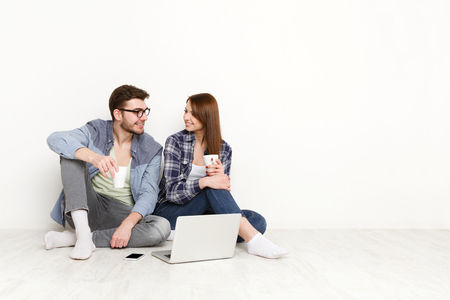 Couple discuss something with laptop and mobile next to them. Happy man and woman sitting on the floor in white interior of their new apartment