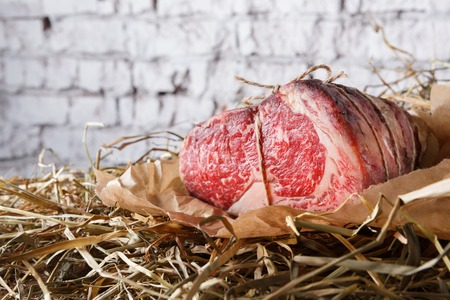 Raw black angus beef bound with rope in craft paper on straw. Aged prime marble meat closeup against white brick wall