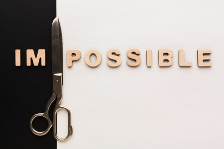 No impossible, only possible concept. Meaning change with scissors on black and white background, challenge, motivation concept