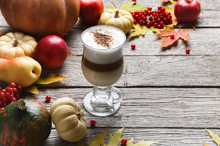 Pumpkin spice latte background. Glass coffee cup with creamy foam, autumn dried leaves, apples and small pumpkins at rustic wood. Fall hot drinks, seasonal offer concept Stock Photo