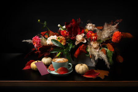 Fall flowers bouquet background on black. Colorful and warm autumn composition with cappuccino, pumpkins and empty postcard on wooden table. Holiday and floral design concept, copy space Stock Photo