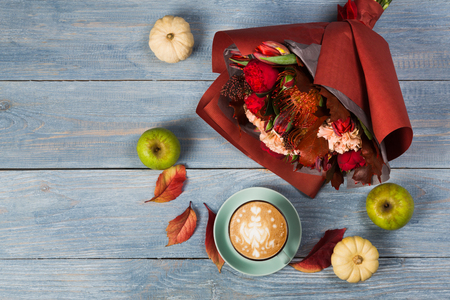 Cappuccino and beautiful flowers bouquet still life. Flower shop composition. Coffee cup, pumpkins and apples on blue wooden background. Florist art and floral design concept, copy space
