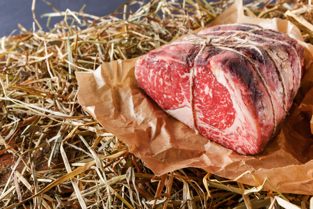 black angus cattle: Raw black angus beef bound with rope in craft paper on straw. Aged prime marble meat closeup Stock Photo