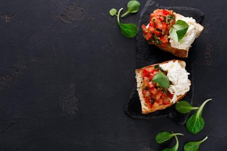 Restaurantvoorgerecht op zwarte achtergrond. Crusty-bruschetta met tomaten, stracciatella-kaas versierd met spinazie. Lekker en gezond eten, bovenaanzicht, kopie ruimte Stockfoto