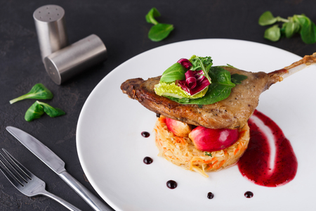Exclusive restaurant meals. Duck confit with braised cabbage, baked apple and cranberry sauce served on snow white plate on black table background, copy space Imagens