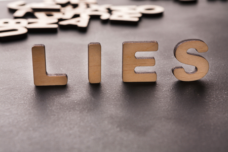 Word Lies standing on table background. Untruth, taradiddle, fake concept Stock Photo