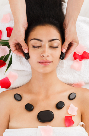 Black marble stone face massage in spa, top view. Female patient in wellness center. Professional massagist make relaxation procedure to beautiful indian girl in beauty parlor Zdjęcie Seryjne