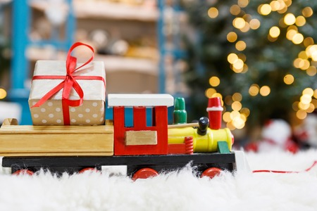 Wooden toy train with christmas gift on snowy decorated background. Selective focus, copy space Stock Photo