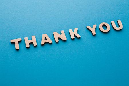 De uitdrukking dankt u op blauwe achtergrond. Beleefdheid, bedankt, dankbaarheid concept